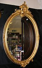 An antique oval gilt framed wall mirror