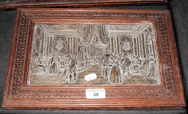 A decorative embossed metal plaque in carved frame