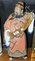 A ceramic oriental figure bearing scroll