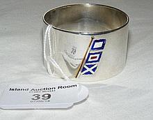 A heavy silver napkin ring with enamel flag