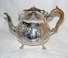 A decoratively embossed Victorian silver tea pot -