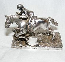 A 9cm silver model of a jumping horse and rider