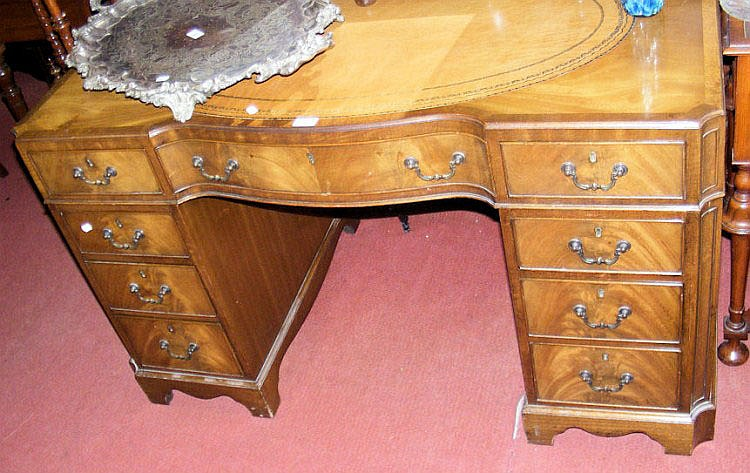 A walnut nine drawer kneehole desk with tooled