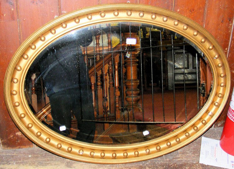 A 102cm x 72cm oval bevelled hanging wall mirror