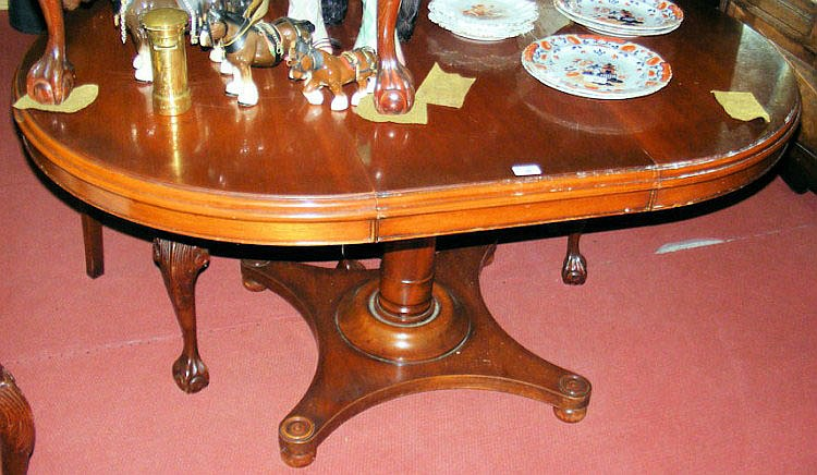 A mahogany extending dining table on pillar