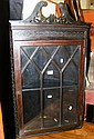 An ebonised hanging corner cabinet enclosed by a