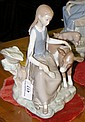 A Lladro china ornament of a seated girl with calf