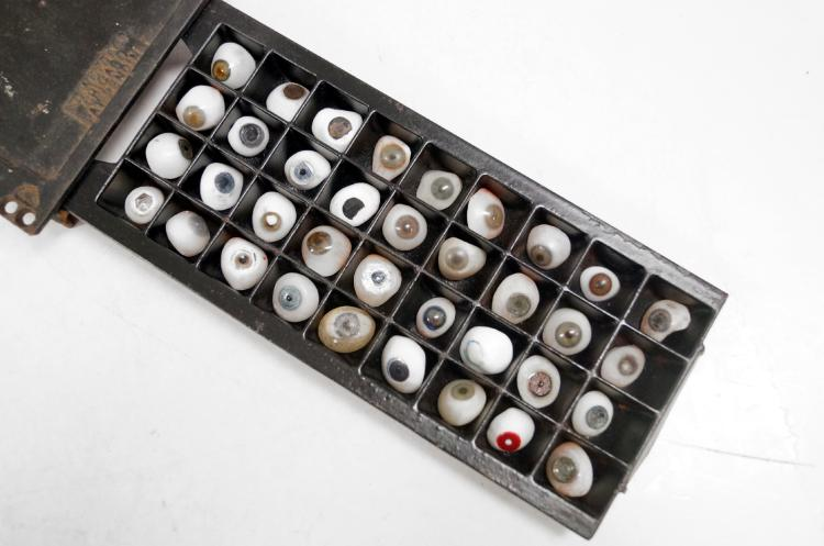 COLLECTION (36) OPTOMETRIST'S PROSTHETIC GLASS EYE SAMPLES INCLUDING CAST IRON STORAGE BOX. BOX/13 1/2 X 6 1/2
