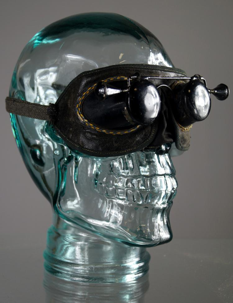 VINTAGE LEATHER METAL HAZING MASK ON CONTEMPORARY GLASS SKULL. HEIGHT 10 1/2