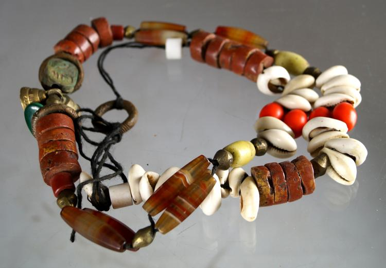 AFRICAN TRADE BEADED NECKLACE INCLUDING AGATE, COWRY SHELLS, HARDSTONE, BRASS AND SCARAB. LENGTH 36