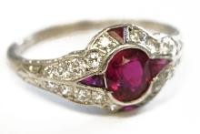 PLATINUM RUBY AND DIAMOND RING CENTERING AN OVAL SYNTHETIC RUBY, WEIGHING APPROXIMATELY 0.80 CT SURROUNDED BY (4) RECTANGULAR CUT RUBIES (APPROXIMATELY 0.15 CT) AND (18 ROUND MELEE DIAMONDS (APPROXIMATELY 0.50/MISSING (2) DIAMONDS). RING SIZE 7; GROSS WEIGHT 3.75 GRAMS
