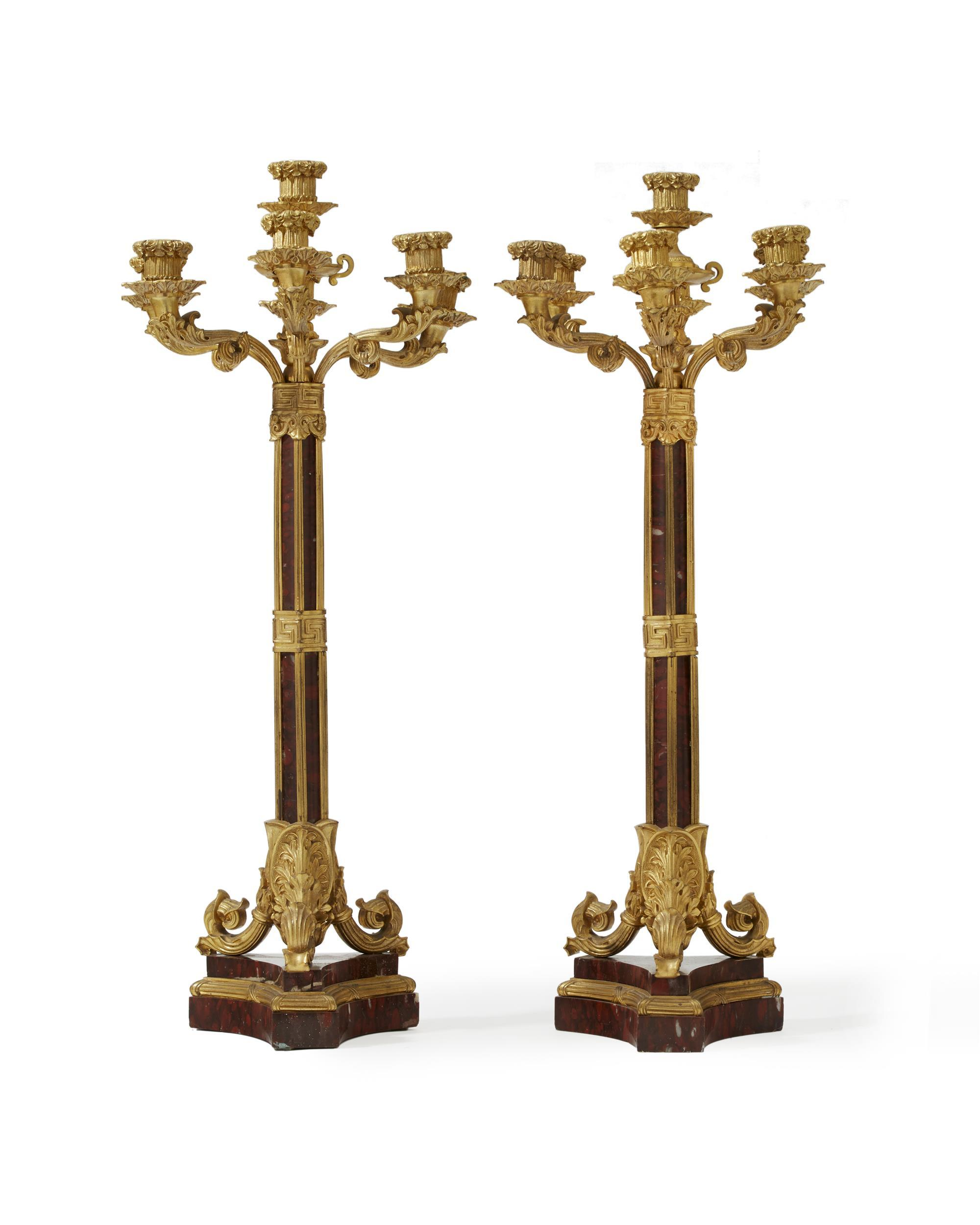A pair of French gilt-bronze and rouge marble candelabra