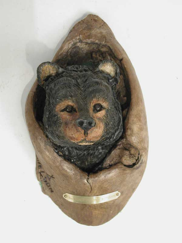 CARVED WOOD SCULPTURE OF BEAR POKING HEAD THROUGH HOLE IN TREE BY JOHN H. KITTELSON (1930-). Appears that this was made to hang on wall. Signed with felt backing. SIZE: 9