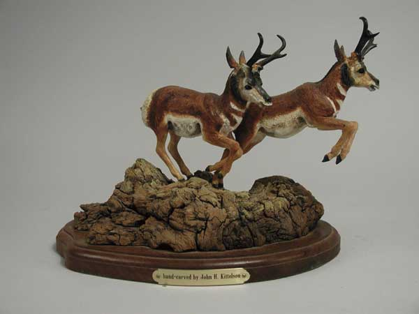 WOOD CARVING OF TWO PRONG HORNED ANTELOPE BY JOHN H. KITTELSON (1930-). Depicts antelope on gnarly wood base. One is in leaping position. Mounted on shaped wooden base. SIZE: 8