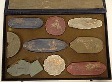 Early 20th Century Chinese Boxed Set of Nine (9) Molded Pottery Inkstones with Parcel Gilt Accents. Each Stone with Molded Design and Calligraphy, Calligraphy to Side Possibly Signature, Box with Calligraphy and Seal Mark. Rubbing to Gilt, Box Damp