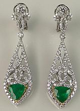 Beautiful Pair of Lady's 2.65 Carat Trilliant Cut Emerald, 2.50 Carat Round Brilliant Cut Diamond and 18 Karat White and Yellow Gold Chandelier Ear Clips. Emeralds with Vivid Saturation of Color. Diamonds E-F Color, VS-SI Clarity. Signed 18K. Very