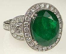Art Deco Style 18 Karat White Gold Emerald and Diamond Ring. Features an Oval Cut Emerald Center Stone with Vivid Green Saturation of Color of Approx. 7 Carats. The Center stone is Flanked by double half moons set with Approx. 2.50 Carats of Diamonds