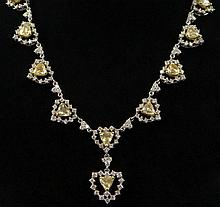 Pretty 18k Gold And Fancy Yellow Diamond Necklace. Each Yellow Diamond is Set in a Heart Shaped jacket of White and Yellow Gold and accented with White Round Brilliant Diamonds. The Fancy Yellow Diamonds of Approx. 16 Total Carat Weight, The White