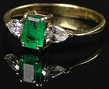 Petite Emerald, Diamond and 18 Karat Yellow Gold Lady's Ring. The Two (2) Pear Shaped Diamonds Weigh Approximately 0.50 Carats of F-G Color, VS1-VS2 Clarity. Size 6-3/4. Signed 750. Few Small Surface Reaching Inclusions or else Good Condition. Weighs