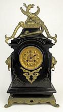 Antique French Onyx and Bronze Mounted Mantle Clock. Interesting Japanese Influence apparent in figural Dragon atop, Figural Lion Ring Handles as well as Japanese Stylized Carving on case. French Movement, and Pretty Filigree Dial. Unsigned. Pendulum