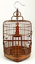 Chinese Carved Wood Birdcage with Porcelain Feeders. Signed to Door and with Fumiki Fine Asian Arts (San Francisco) Retail Tag. As New Condition. Measures Approximately 26 Inches Tall and 13 Inches Wide at Base. We will not ship this item due to its