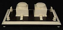 Ebony and Ivory Double Inkwell Desk Stand. Two (2) Ivory Inkwells and Two (2) Ivory Pen Holders Mounted on a Ebony Base Supported by Four (4) Ivory Ball Feet. Unsigned. Measures 3-1/2 Inches Tall by 10-1/2 Inches Long and 5-1/4 Inches Wide. 1 Hinge