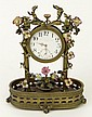 Early 20th Century French Small Bronze Desk Clock with Painted Porcelain Dial and Porcelain Flower Decoration. Movement Signed France, Ancre 12 Rubis, Octava, U.S.A.R.816321 and Numerals #P. 33103-D.R.P.175275 and #18188. Also Stamped France Two (2)