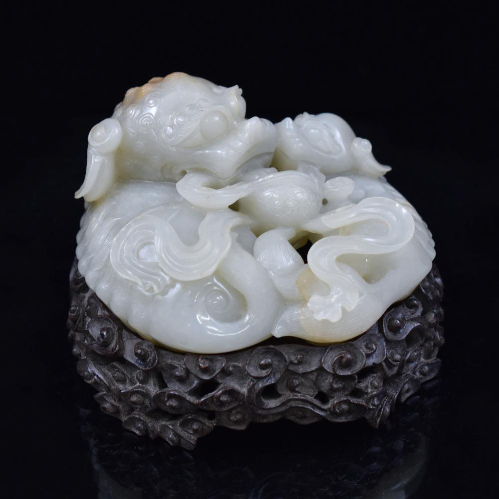 CARVED WHITE JADE OF THREE FOO-DOGS ON STAND