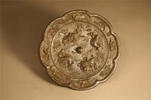 A BRONZE MIRROR WITH BEASTS AND BIRDS MOTIF