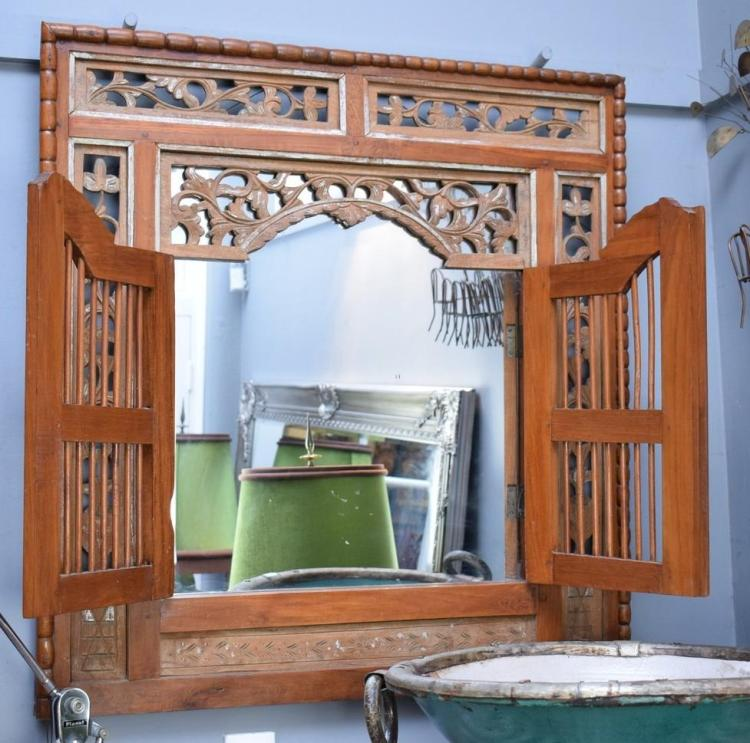 A DECORATIVE INDONESIAN TEAK WALL MIRROR AND STEPLADDER