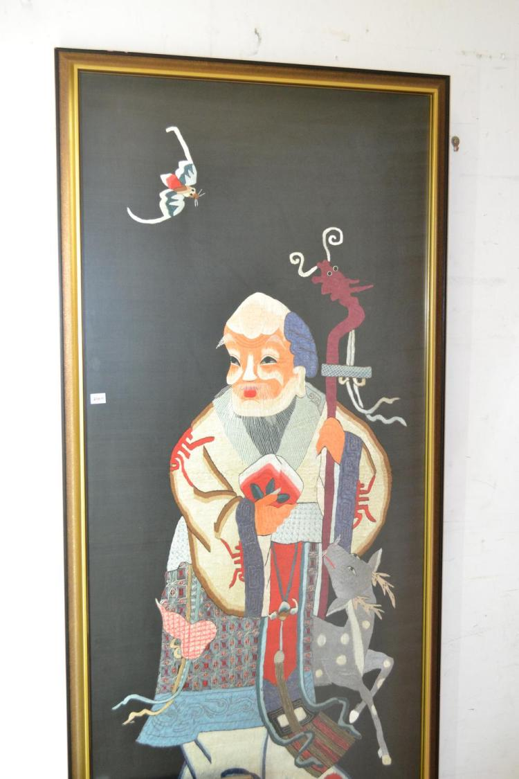 A CHINESE SILK EMBOIRDED FRAMED WORK OF A MAN AND A DEER