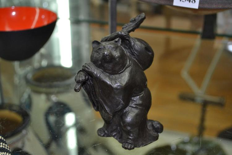 A BRONZE FIGURE OF A BADGER CLASPING RUCKSACK AND CLAD IN CLOAK