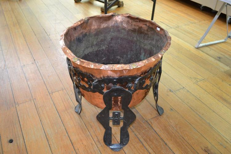 A COPPER FIREWOOD JARDINIERE ON WROUGHT IRON STAND