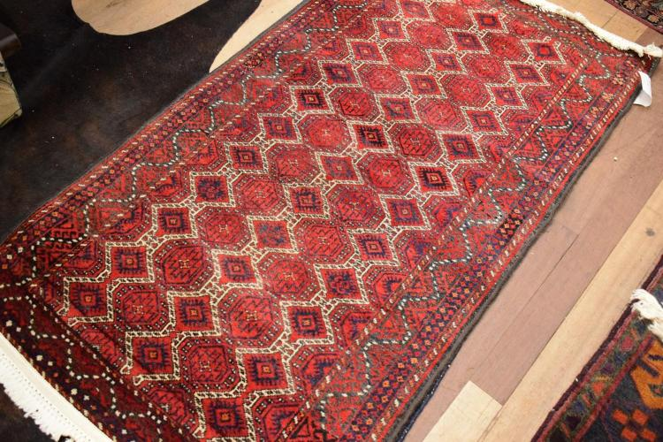 A PERSIAN STYLE RUG IN RED DIAMOND PATTERN