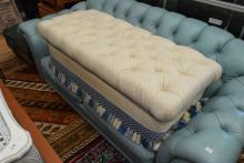 A CREAM AND BLUE OTTOMAN WITH TASSLES
