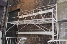 A WHITE WROUGHT IRON OUTDOOR BENCH SEAT