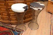 AN IRON BAR STOOL IN COW HIDE UPPHOLSTRY