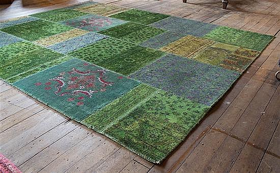 A PATCHWORK RUG IN TONES OF GREEN AND BLUE