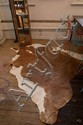 A BROWN AND WHITE COWHIDE RUG