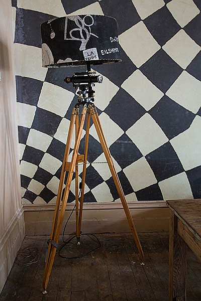 A TALL LAMP ON A VINTAGE THEODOLITE TRIPOD BASE WITH HAND-PAINTED LAMPSHADE