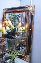 A DECORATIVE GILT AND BLACK PAINTED MIRROR