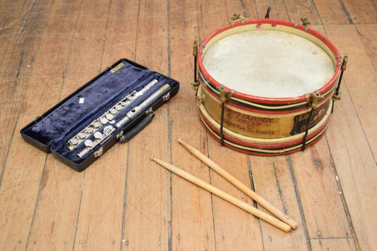 A vintage snare drum with drum sticks and a flute in case for Classic house drums