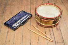A VINTAGE SNARE DRUM WITH DRUM STICKS AND A FLUTE IN CASE