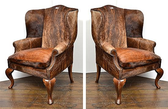 A PAIR OF WINGBACKED CHAIRS UPHOLSTERED IN HIDE
