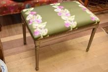 A LOUIS XVI STYLE STUDDED UPHOLSTERED OTTOMAN