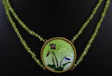 AN ART NOUVEAU FLORAL ENAMEL PENDANT SUSPENDED FROM A DOUBLE ROW OF PERIDOT BEADS.