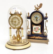A ANNIVERSARY CLOCK AND PORCELAIN MANTLE CLOCK WITH CHERUB MOTIFS