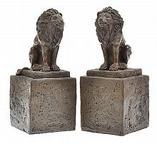 A PAIR OF COMPOSITE LIONS ON SOCLES