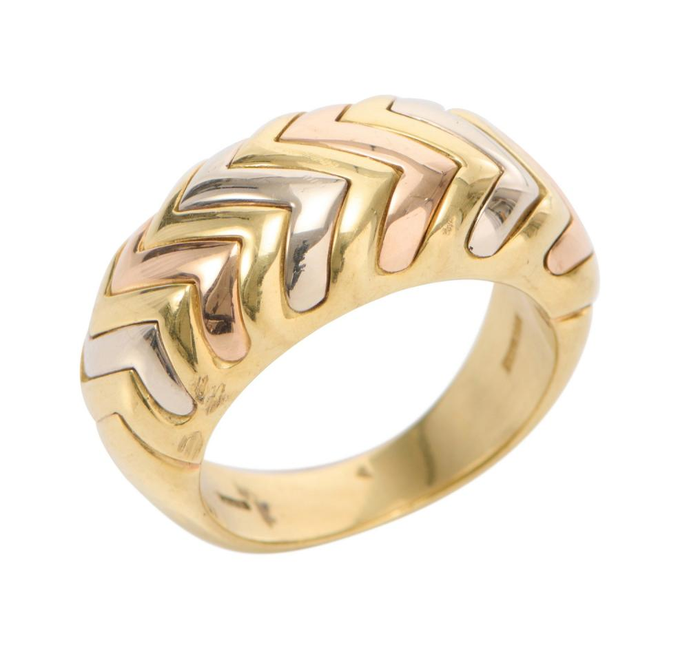 A 'SPIGA' RING IN TRI-COLOUR 18CT GOLD BY BULGARI, OF TAPERING DOMED DESIGN, WITH INTERLOCKING ZIG-ZAG LINKS IN ALTERNATING TRI-COLO.