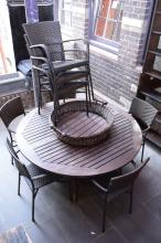 AN OUTDOOR SETTING COMPRISING OF CIRCULAR TIMBER TABLE, EIGHT CHAIRS, & A MATCHING BASKET